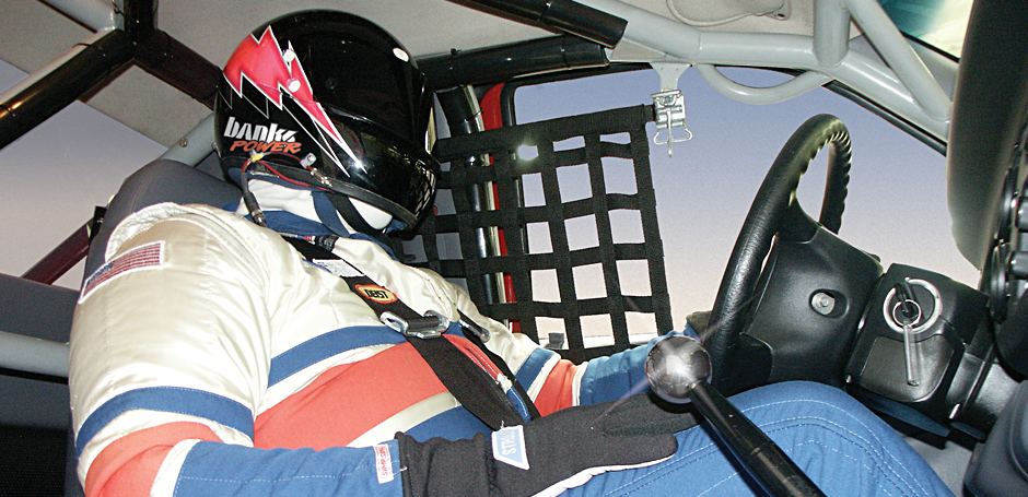 The driver has one hand on the wheel and one on his knee at 220 mph! Now that's steady.